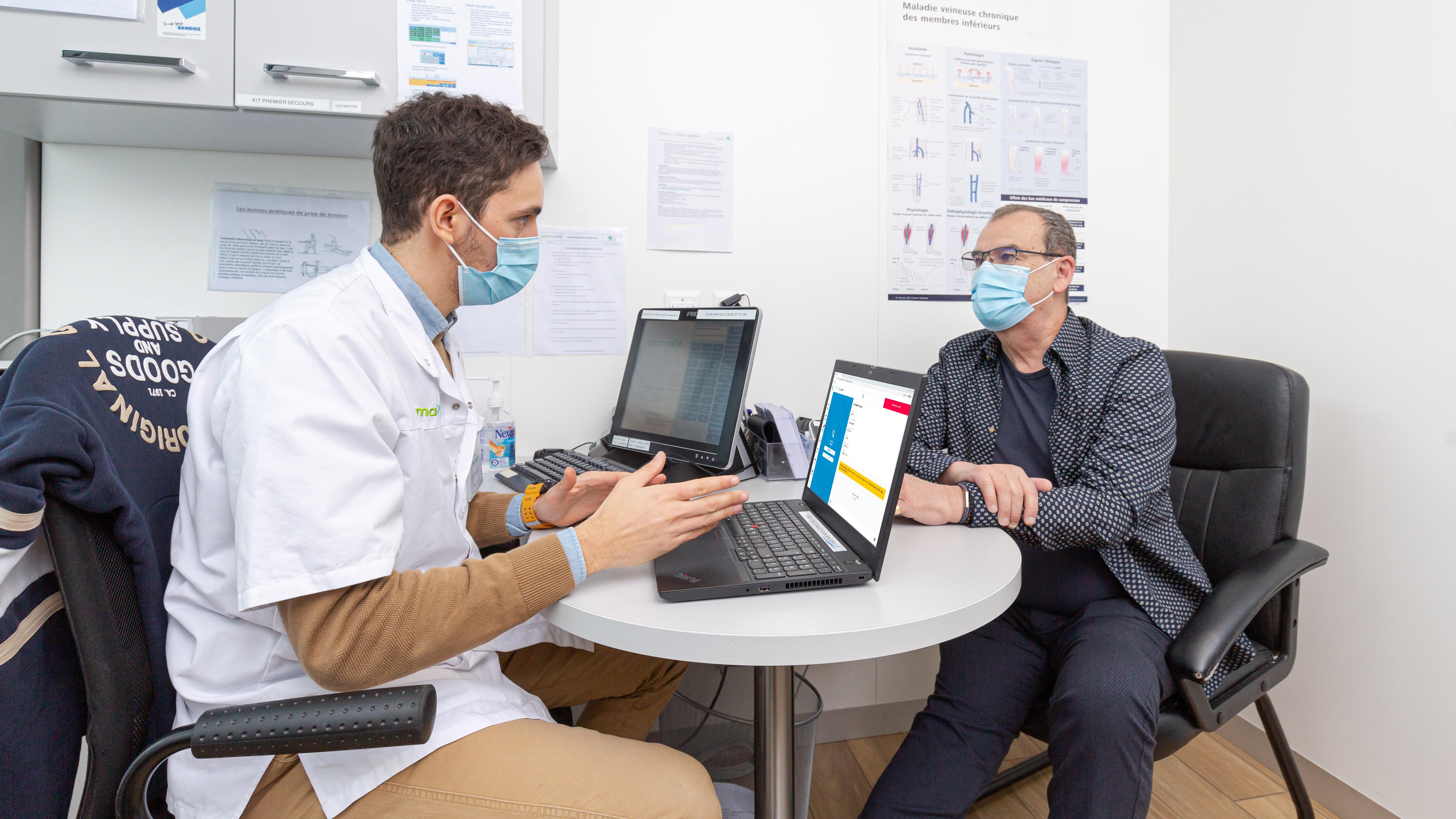 Le pharmacien explique le fonctionnement de la téléconsultation à son patient.